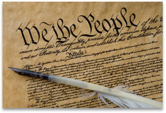 "An image of the Consititution with ""We The People"" highlighted, and a quill on top."